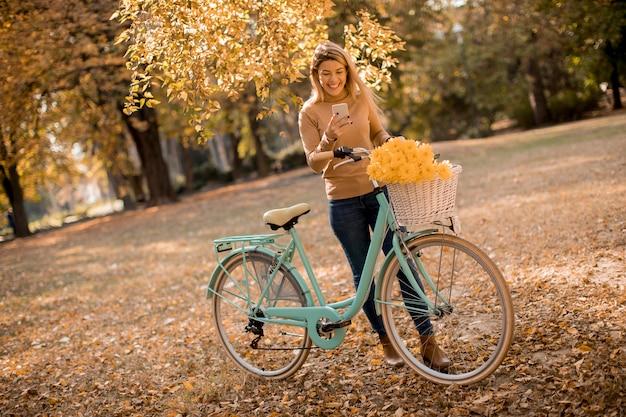 秋の公園でスマートフォンを使用して自転車を持つ若い女性 Premium写真