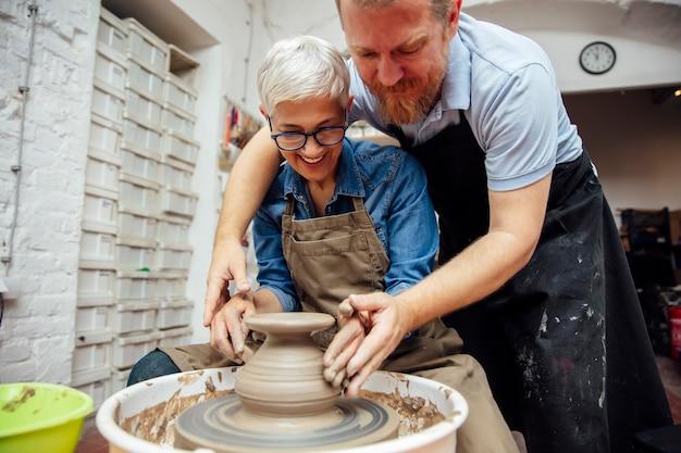 陶芸教室の先生とホイールに粘土を回転している年配の女性 Premium写真