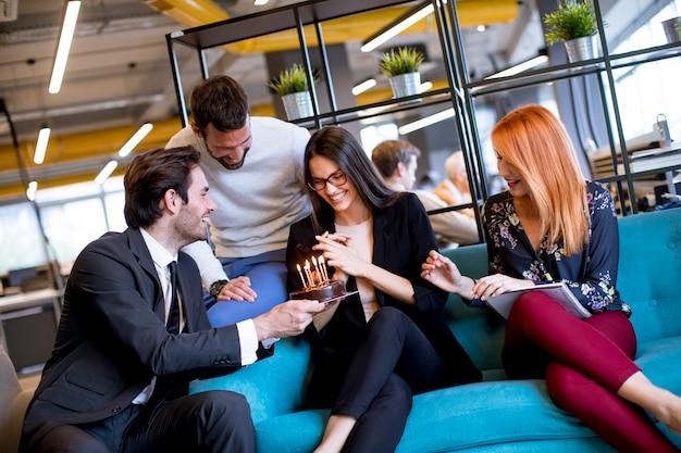 ケーキと近代的なオフィスで若い女性の同僚の誕生日パーティー Premium写真