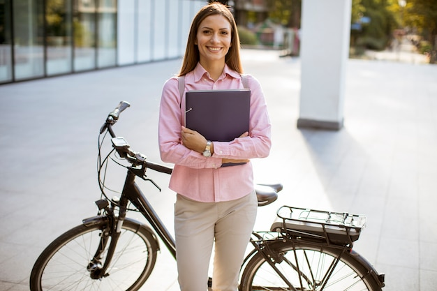 電動自転車の横に屋外に立っている手でファイルを持つ若い女性 Premium写真