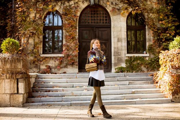 秋の公園を歩いてかなり若い女性 Premium写真