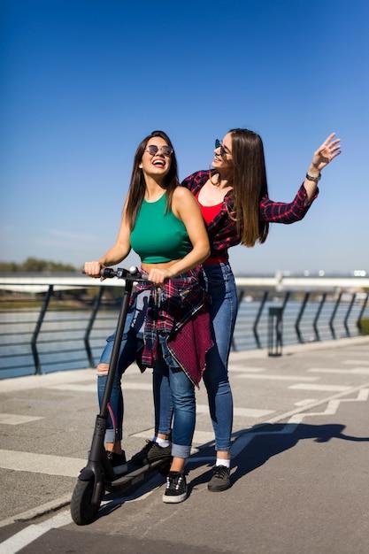路上で電動スクーターに乗ってかなり若い女性の友人 Premium写真