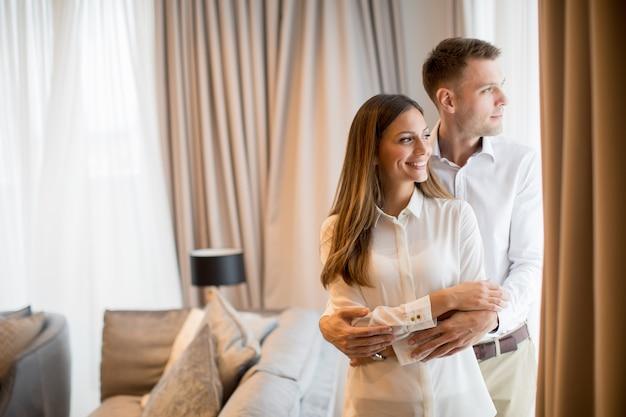 現代的なアパートのリビングルームで立っているを受け入れるカップル Premium写真