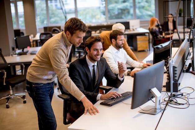 Старший бизнесмен и молодые бизнесмены работают в современном офисе Premium Фотографии