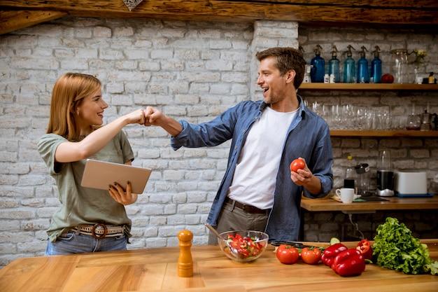 素敵な陽気な若いカップルが一緒に夕食を作って、デジタルタブレットでレシピを見て、素朴なキッチンで楽しんで Premium写真