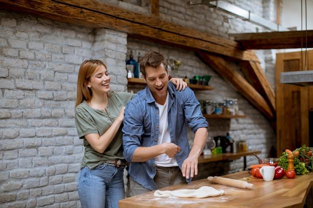 素敵な陽気な若いカップルが一緒に夕食を準備し、素朴なキッチンで楽しんで Premium写真