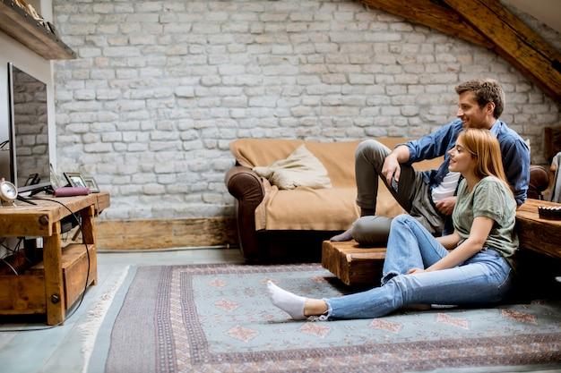 笑顔の素敵な若いカップルリラックスして自宅でテレビを見て Premium写真