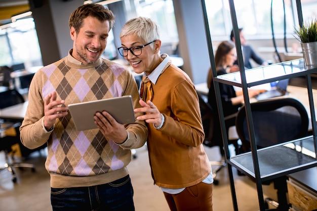 シニアビジネスの女性と彼女の若い同僚がデジタルタブレットでオフィスに立っています。 Premium写真