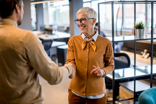 若いビジネスマンとオフィスで握手シニアビジネス女性 Premium写真