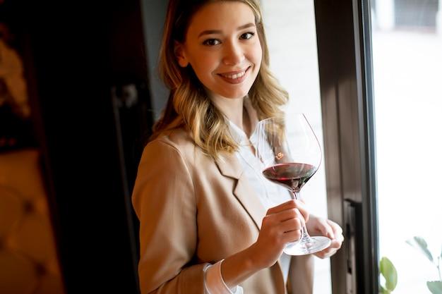 窓の近くに立って、よそ見赤ワインのグラスを持つ単一のかなり若い女性 Premium写真