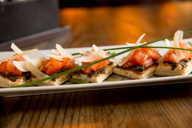 Брускетта с песто из оливок и чеснока, с помидорами черри и листьями пармезана Premium Фотографии