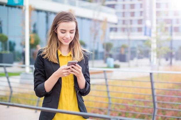 Исполнительный работает с мобильным телефоном на улице с офисными зданиями Premium Фотографии