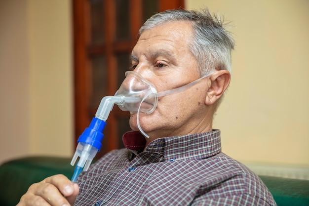 Старший мужчина с помощью медицинского оборудования для ингаляции с респираторной маской, небулайзер Premium Фотографии