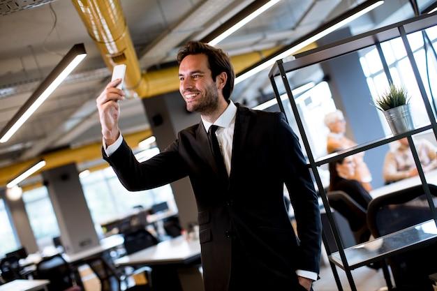 オフィスで現代のスマートフォンを使用して黒のスーツを着ている青年実業家 Premium写真