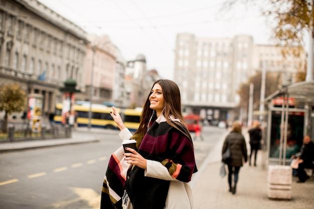 Молодая женщина, приветствуя такси на улице в городе Premium Фотографии