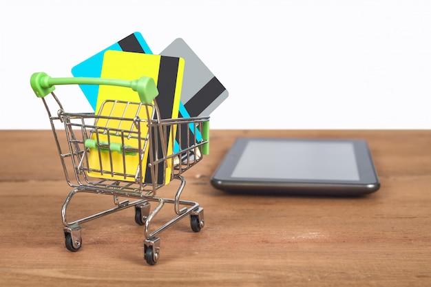 ショッピングカートのトロリーにクレジットカードまたはデビットカード。 Premium写真