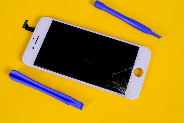 背景に壊れた、ひびの入った液晶携帯画面。 Premium写真