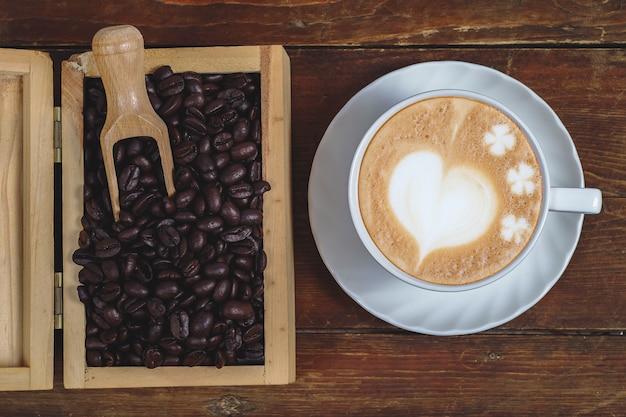 古い木材の背景に遅いアートコーヒーの木箱にコーヒー豆。 Premium写真