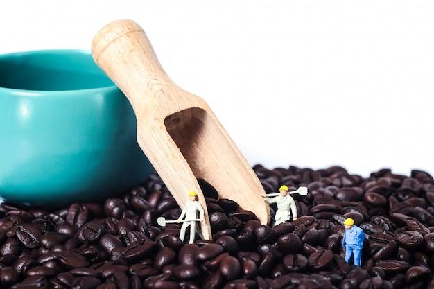 Миниатюрный работник работая на свежих кофейных зернах на белой предпосылке. Premium Фотографии