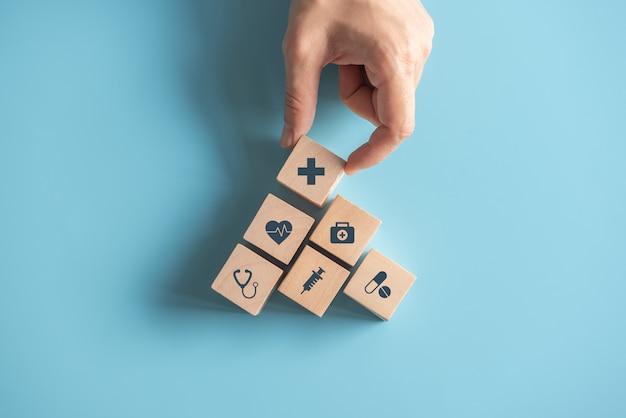 健康保険の概念、青い壁に医療医療アイコンとウッドキューブスタッキングを配置する女性の手、コピースペース。 Premium写真