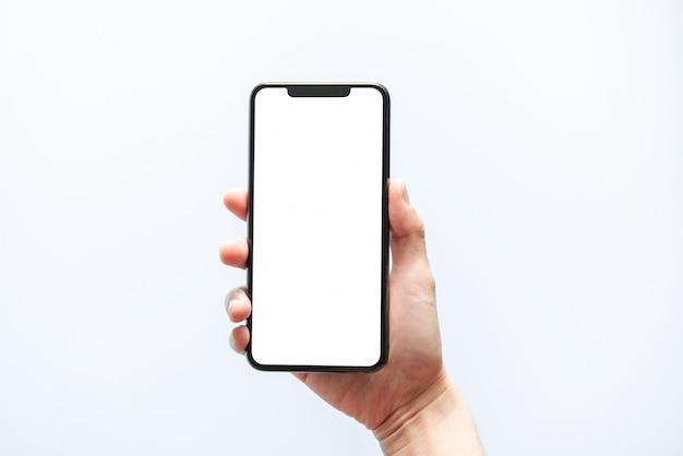 スマートフォンのモックアップ。黒い電話の白い画面を持っている手を閉じます。白い背景で隔離されました。携帯電話フレームレスデザインコンセプト。 Premium写真