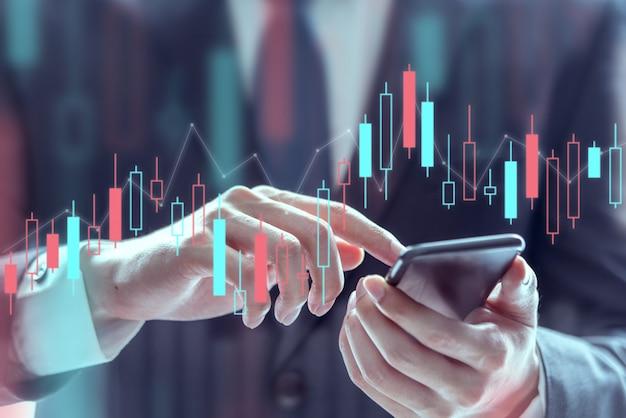 携帯電話を使用して株式市場データ、テクニカル価格グラフおよびインジケーターを確認するビジネスマン Premium写真