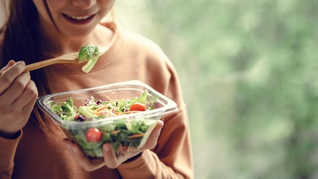 健康食品のサラダを食べる女性をクローズアップ、サラダとフォークに焦点を当てます。 Premium写真