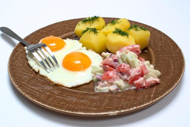 揚げた卵、ディルとジャガイモ、スライストマトとサラダと古い茶色のプレートにキュウリ Premium写真