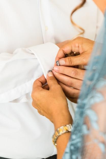 彼が彼の結婚式の日に服を着るようにカフスボタンを身に着けている新郎。新郎のスーツ Premium写真