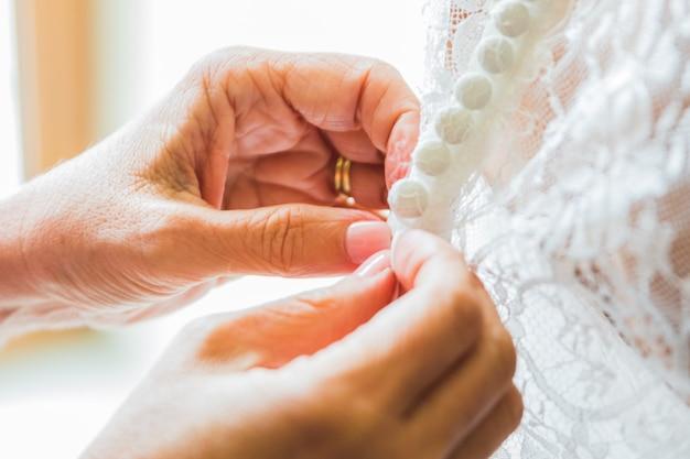 花嫁介添人花嫁のコルセットを締め、彼女のドレスを取得 Premium写真