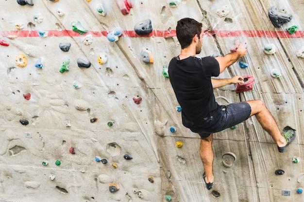 男は室内の人工壁にロッククライミングを練習します。アクティブなライフスタイルとボルダリングの概念 Premium写真