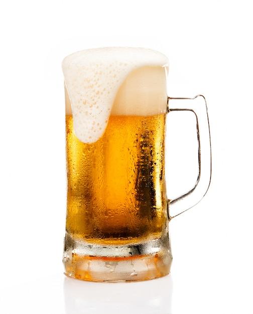 白い背景で隔離のガラスの上の泡の泡とビールのジョッキ Premium写真