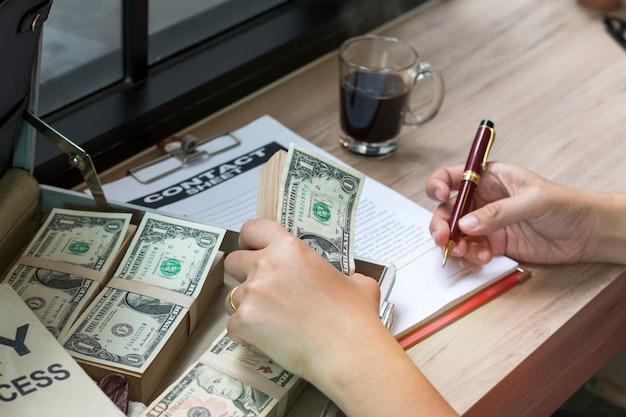 ビジネス文書やコンタクトシートを書くためにペンを持つビジネスマンの手 Premium写真