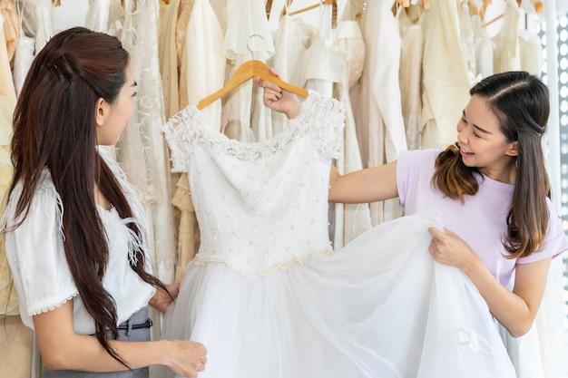 テーラーアシスタントとショップでドレスを選択するアジアの女性の肖像画。 Premium写真
