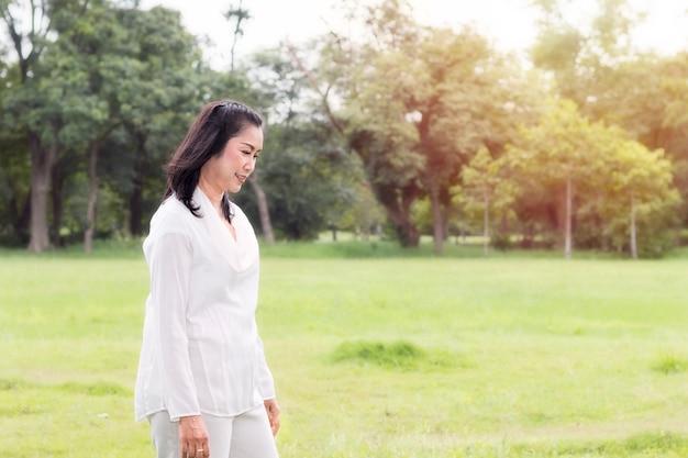 笑みを浮かべて、公園でリラックスした素敵な中年の女性の美しい肖像画。 Premium写真