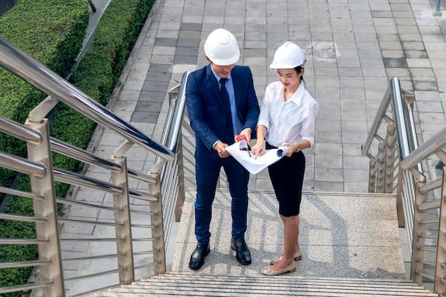 マネージャーの女性のハンサムなアジアビジネスエンジニアは笑みを浮かべて、パートナーと成功について話します。 Premium写真