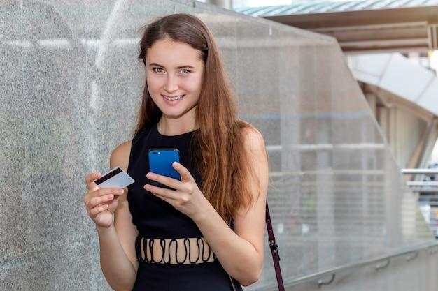 クレジットカードとスマートフォンアプリケーションをオンラインで購入するスマートな白人女性。 Premium写真