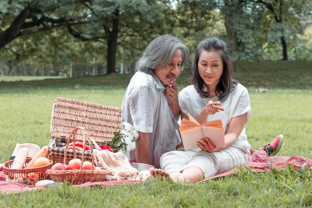 本を読んで年配のカップルと公園でのピクニック。 Premium写真