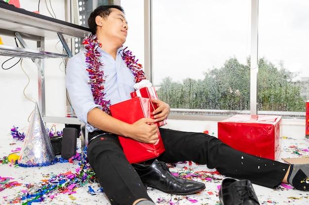 パーティーが二日酔いのとき。パーティーの後、床で寝ている男。 Premium写真