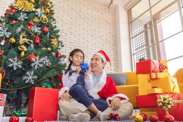 父はサプライズして、クリスマスの時期にギフトボックスを娘に送りました。 Premium写真