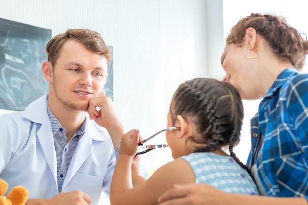 病院で聴診器を使用して小さな女の子患者を調べる小児科医(医師)男。 Premium写真