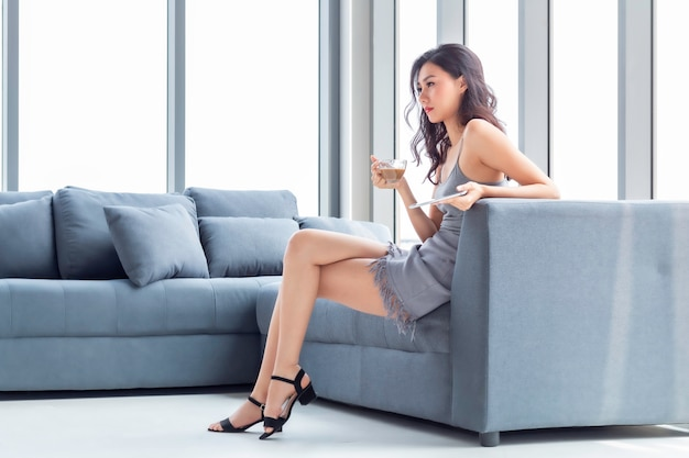 コーヒーを飲みながら、リビングルームでタブレットとオンラインショッピングの美しい女性。 Premium写真