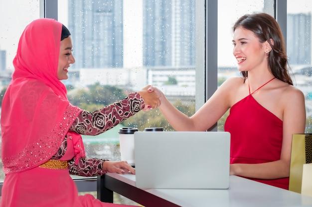 買い物袋の近くに座っている白人の友情と握手する若いイスラム教徒の女性 Premium写真