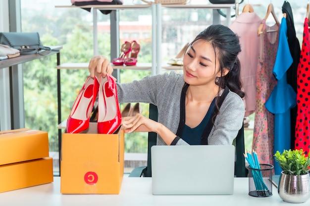 幸せなアジアのカジュアルな女性のスタートアップのスモールビジネス起業家中小企業の洋服店で働いています。 Premium写真