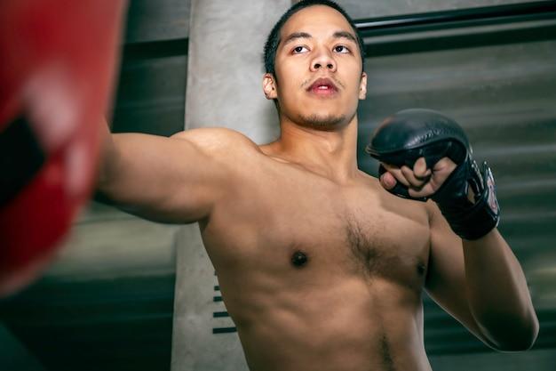 フィットネスジムでサンドバッグトレーニングアスリートアジア男ボクサー。 Premium写真