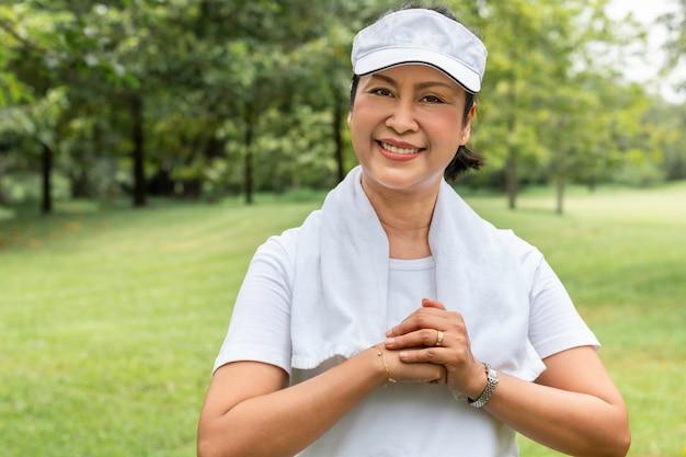 Красивый азиатский портрет старшей женщины думая и ослабляя на парке. Premium Фотографии