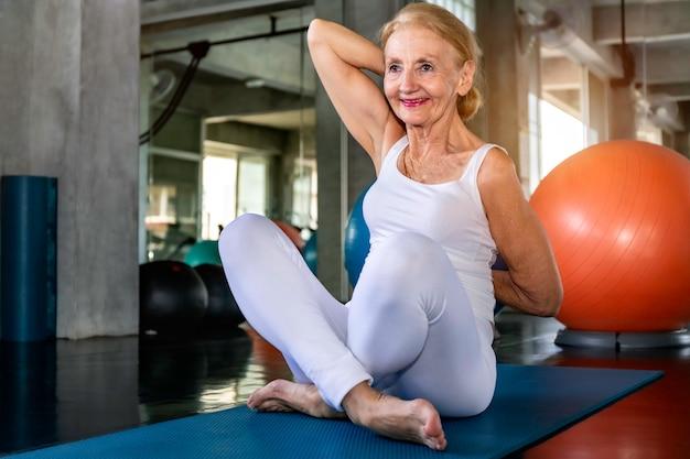 フィットネスジムでヨガの練習をしている白人の年配の女性。 Premium写真