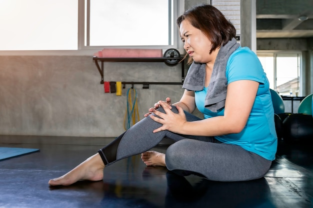 フィットネスジムでトレーニング中に年配の女性アジアの足の痛み。 Premium写真