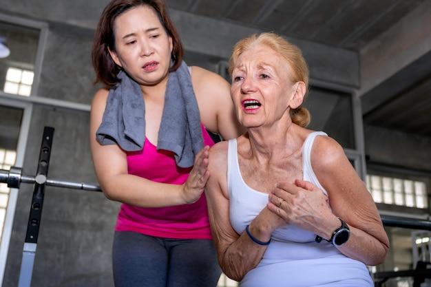 フィットネスジムでアジアの友人とトレーニング中に年配の女性白人心臓発作。 Premium写真