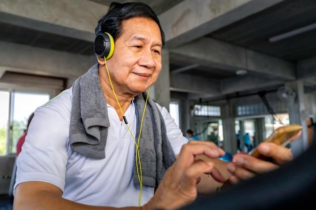 スポーツウェアのシニアアジア人は、フィットネスジムで音楽やトレーニングサイクリングカーディオに耳を傾けます。 Premium写真